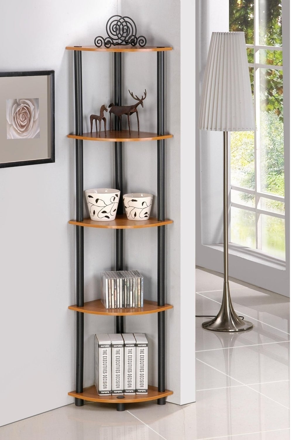 The shelf with five brown shelves and black tubes connecting them in the corner of the room with trinkets on it