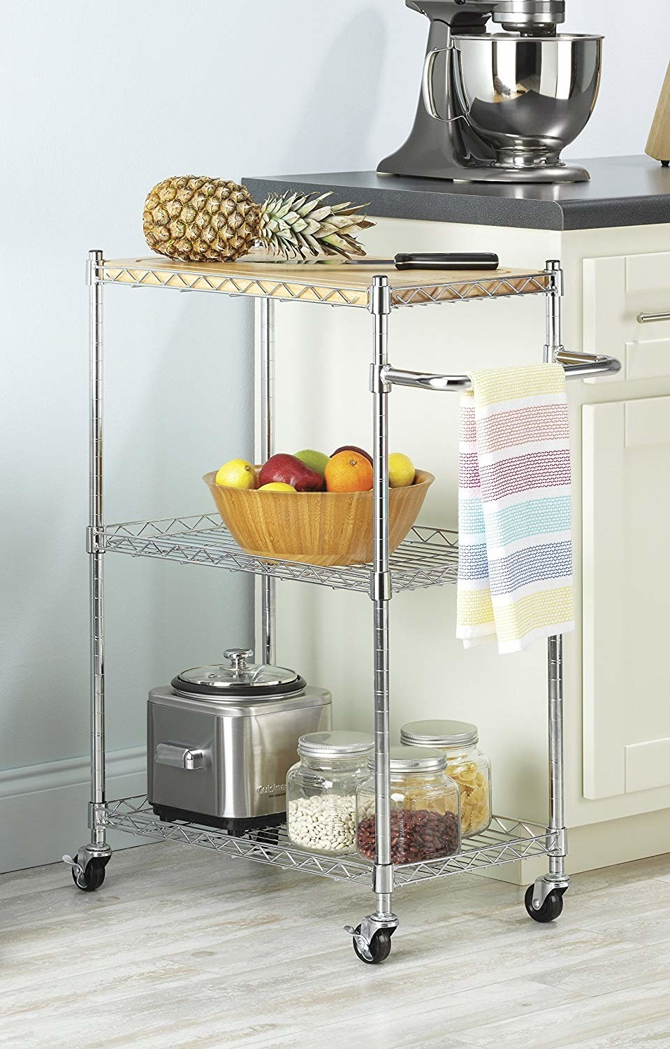 The silver metal three-tier kitchen cart with a wood cutting board on top and assorted kitchen products on it