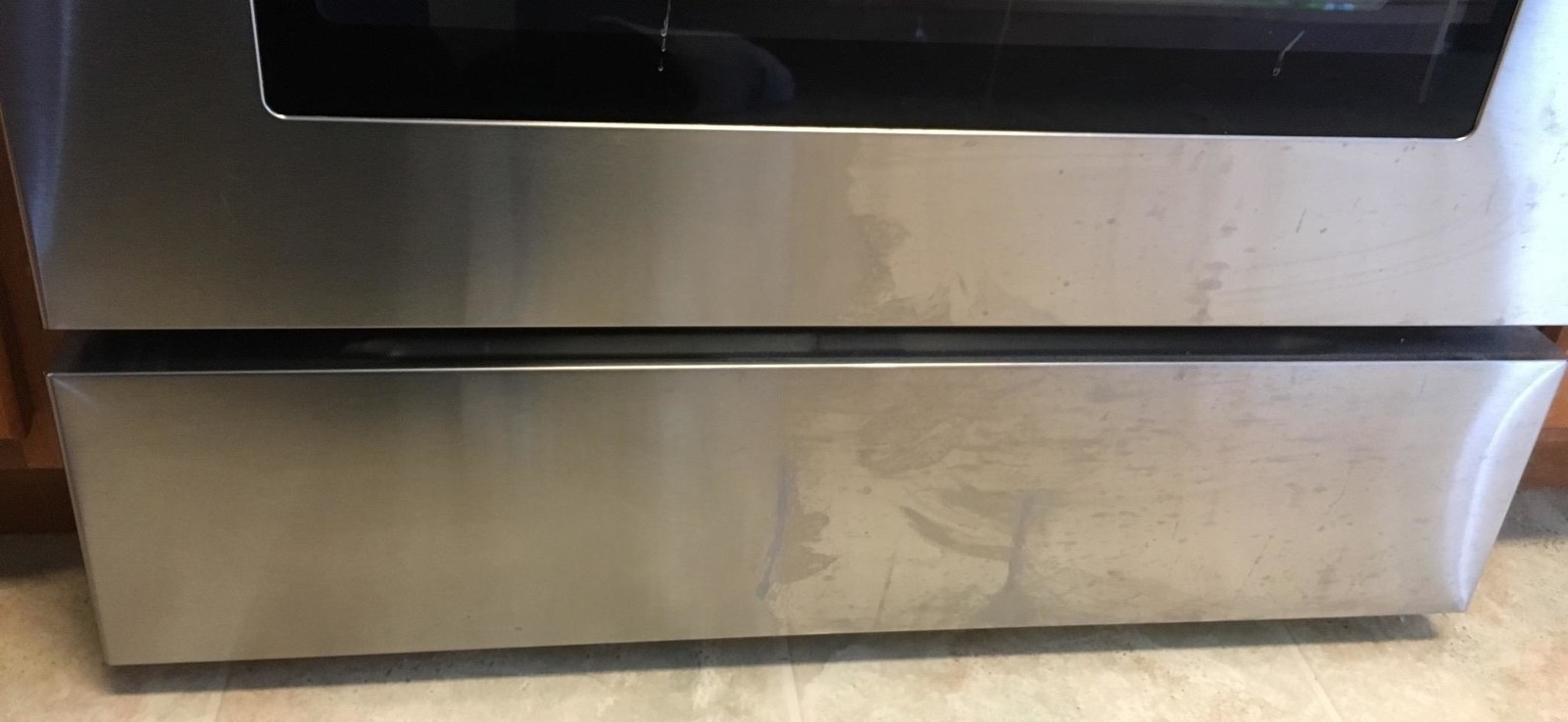 Reviewer photo showing a stainless steel oven partially polished by the cleaner to demonstrate how well it works. The non-polished side is covered with stains