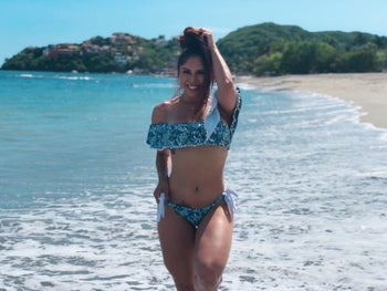reviewer wearing the off-the-shoulder bikini in blue print