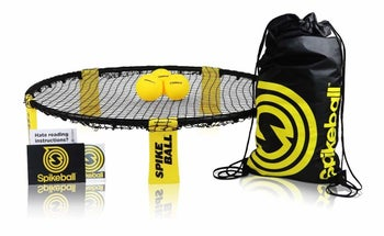a small circular netted trampoline with a black and yellow storage bag and three small yellow balls