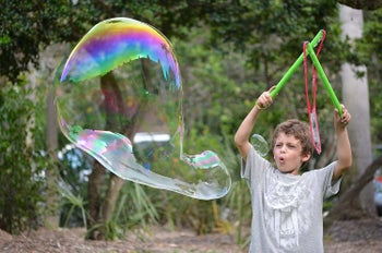 a child holding two wands in the air making a big bubble
