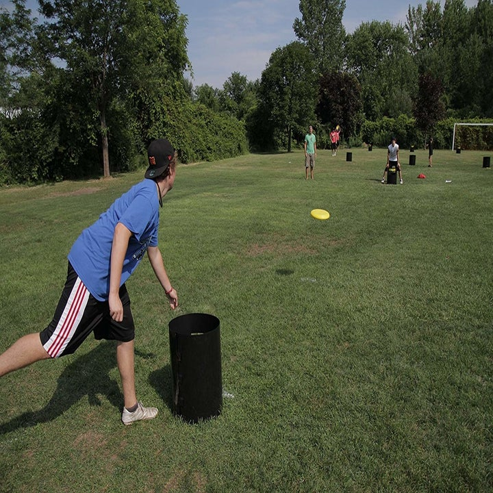 a person lunging over a black kan jam tube while throwing a yellow frisbee to someone across from them in a grassy field