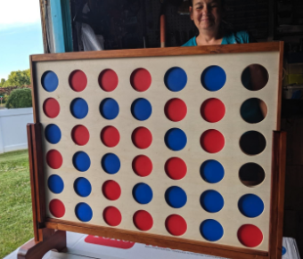 a wooden oversized connect four board game with the open circles filled with either red or blue tokens