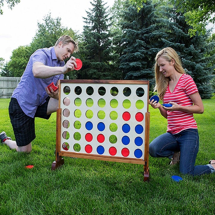 a couple is kneeling in the grass playing with an oversized version of the game connect four. the board includes many open circle slots where blue and red tiles are place inside