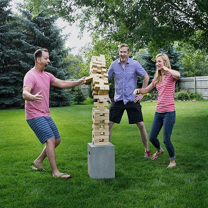 three people outside in the grass playing with a very tall tower of blocks