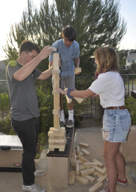 three people outside in the grass playing with a very tall tower of blocks but from a sideways view