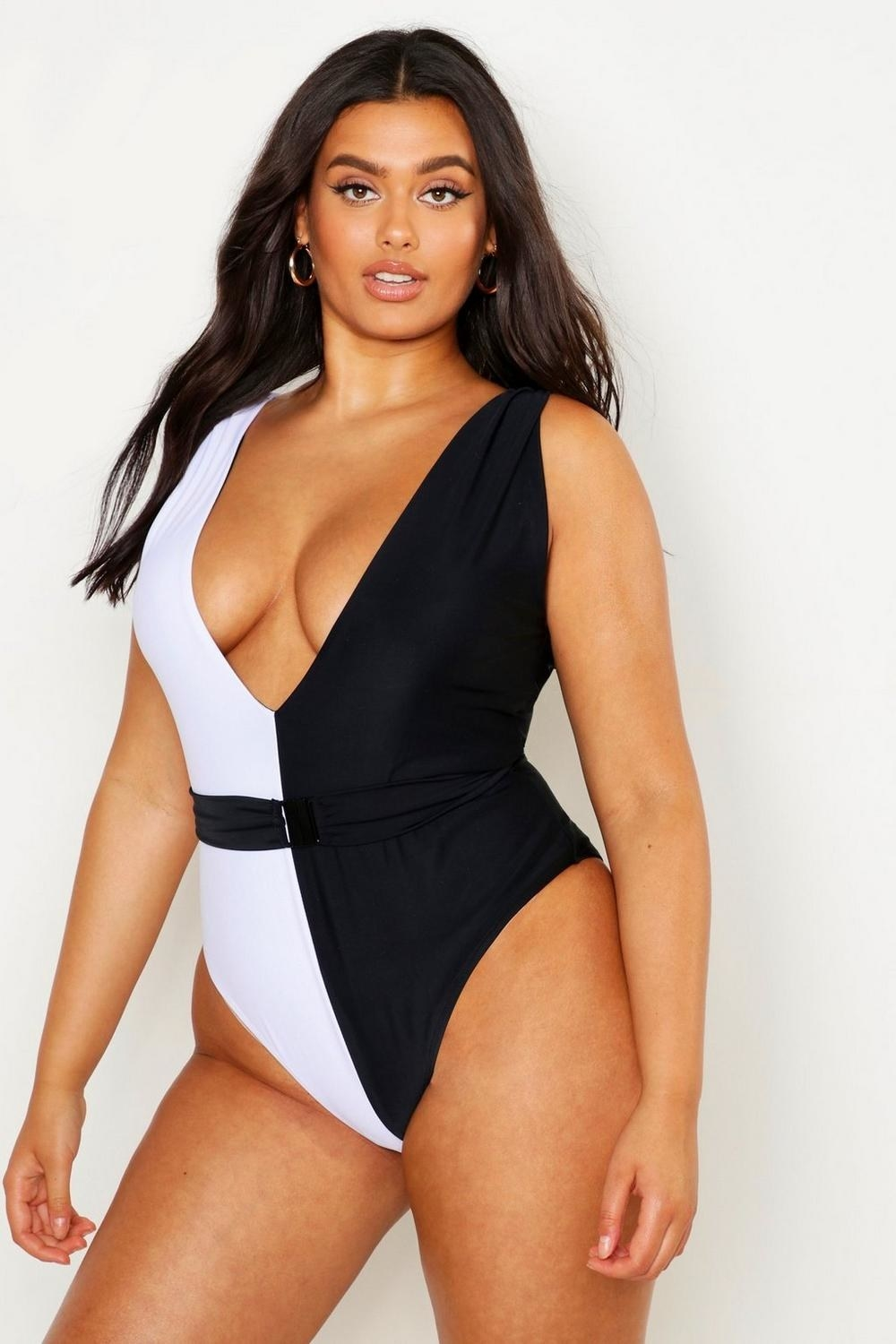 model wears one piece that is split vertically and half black and half white with a black belt