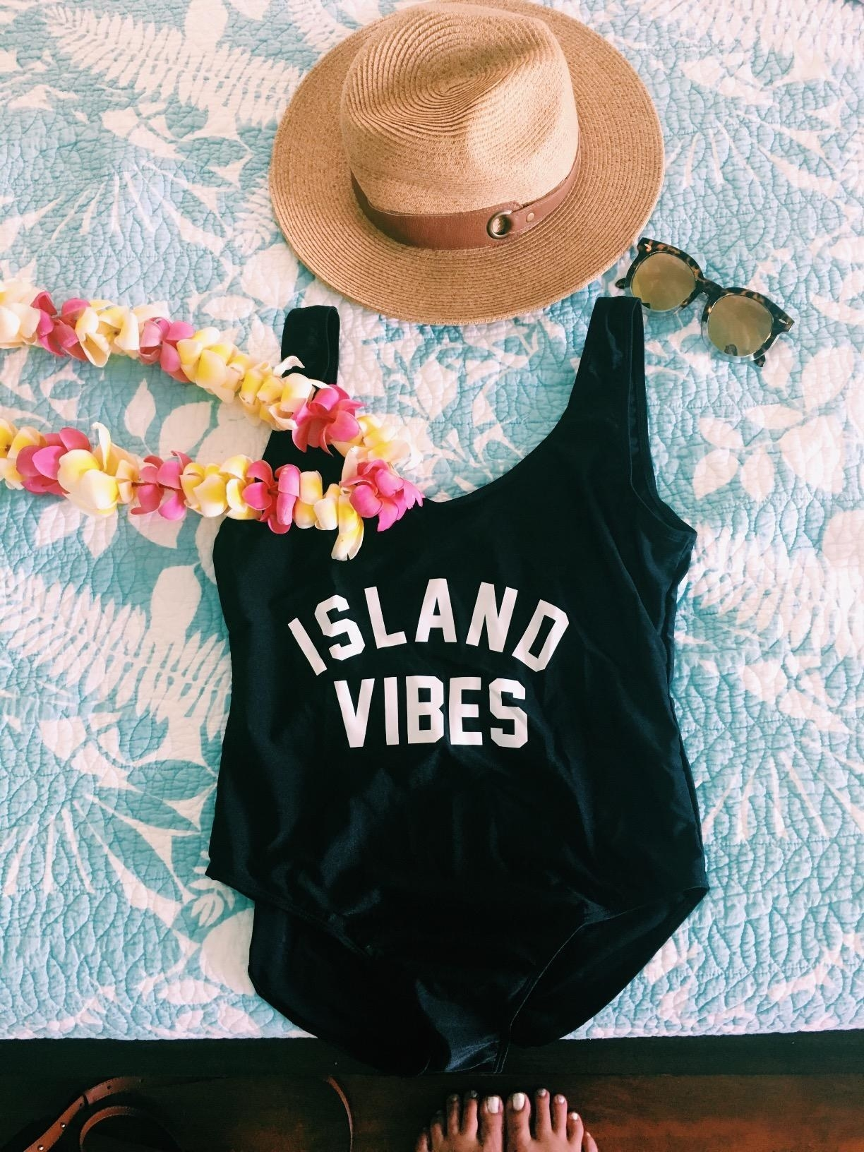black one piece that says island vibes