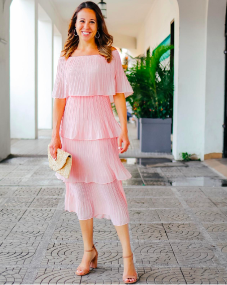 A reviewer wearing the midi dress, which is made up of four tiers, in pink