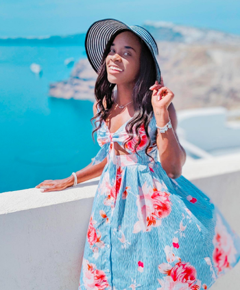A reviewer wearing the spaghetti strap dress with bust cutout in blue with bold pink flowers