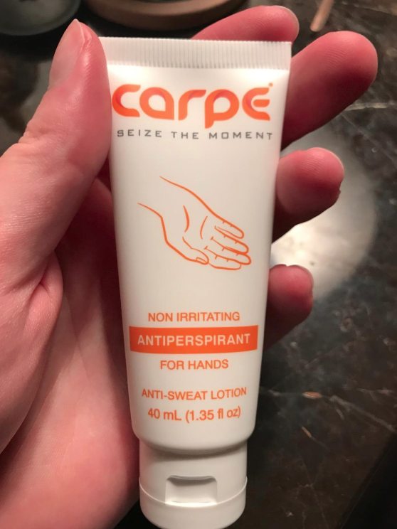 Reviewer holding the Carpe antiperspirant for hands