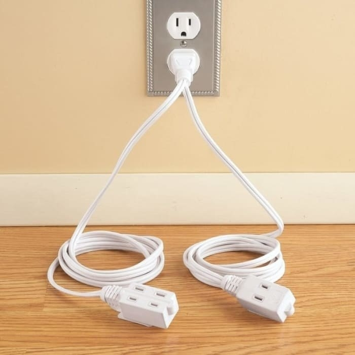 A cord plugged into one socket that splits off into two extension cords