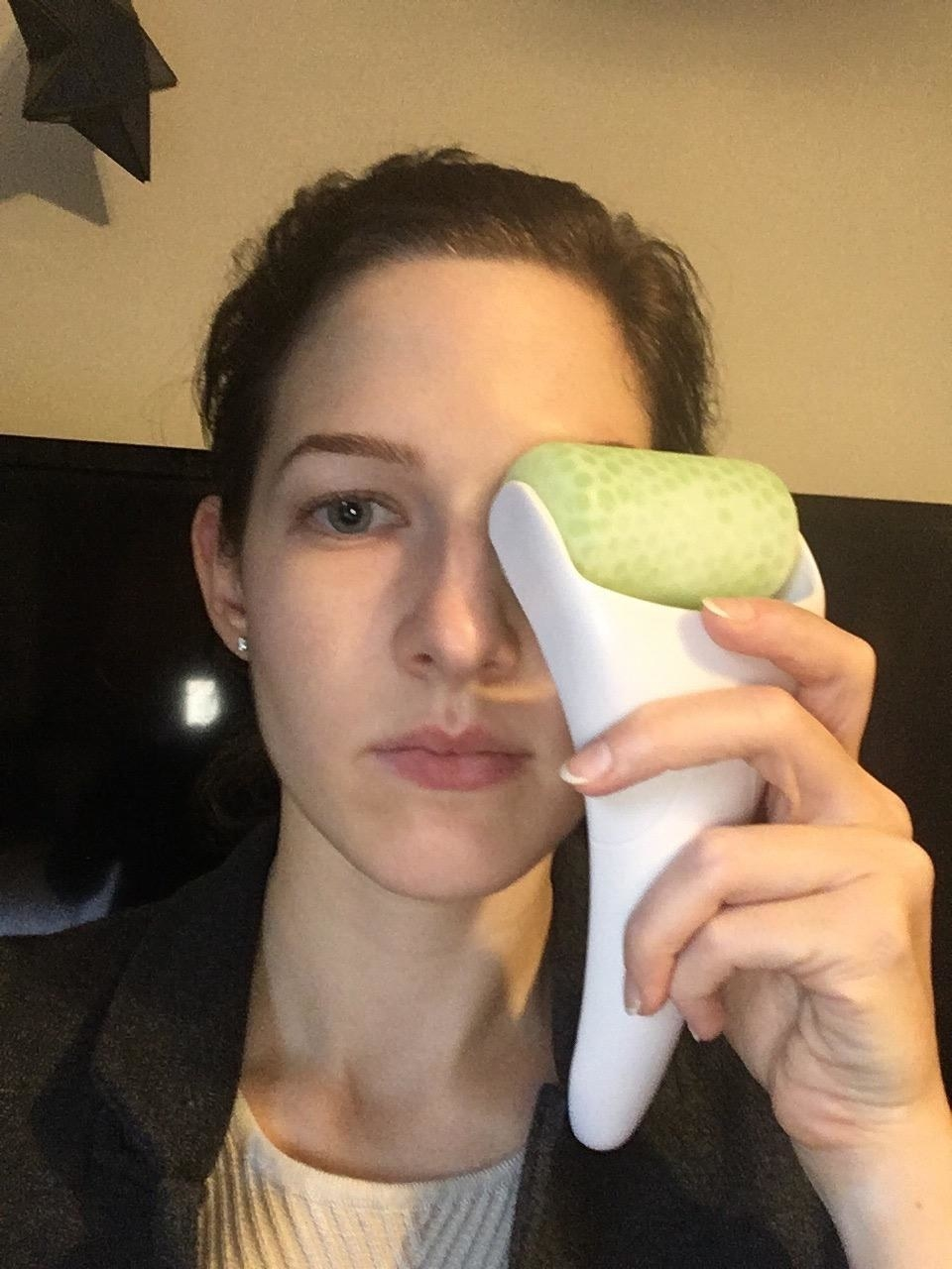 A reviewer using the roller on their eye
