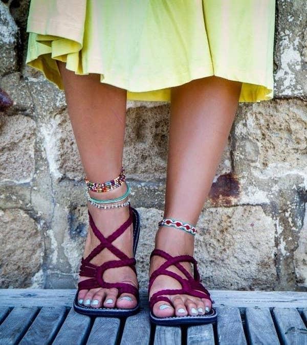 model wears sandals in sunset sangria