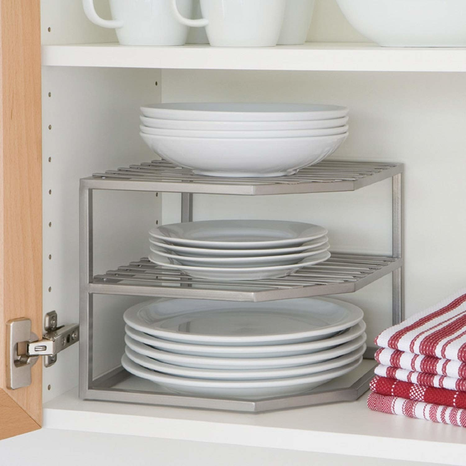 inside a kitchen cabinet with a corner view of the three-tier dish organizer holding heavy looking dinner plates, salad plates, and bowls