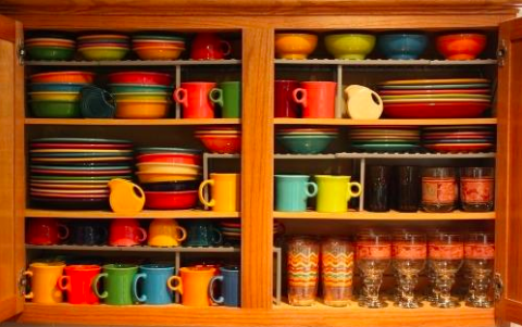 reviewer pic of colorful, heavy fiesta ware dishes inside a kitchen cabinet safely organized in stacks with the help of the shelves