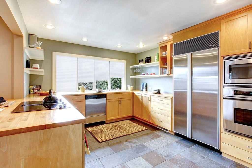 A kitchen with the light filtering pleated fabric shades on all the windows.