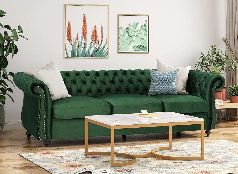 A lush green velvet chesterfield sofa.
