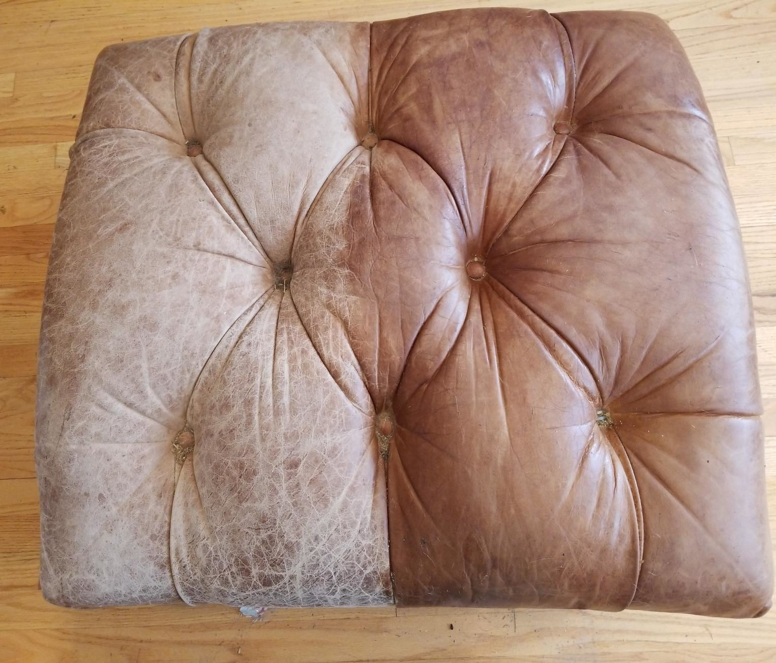 A tufted leather ottoman, the right half greyish and old leather, the right half a rich brown leather after conditioning