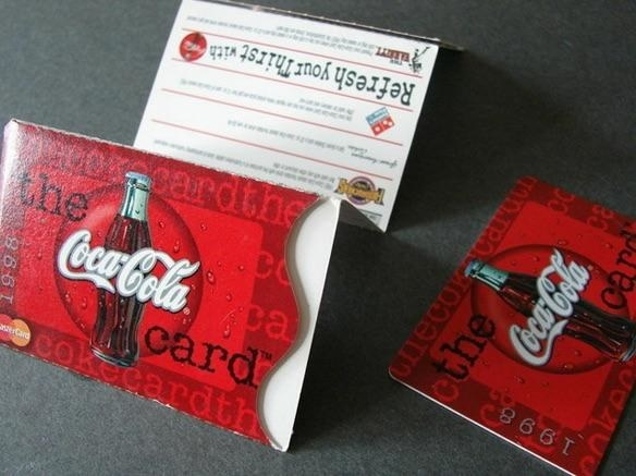A close of a Coca-Cola Rewards card and the cardboard envelope for it.