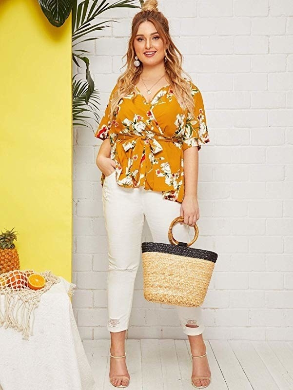 The wrap blouse in a mustard yellow floral print with sleeves that hit at the elbows