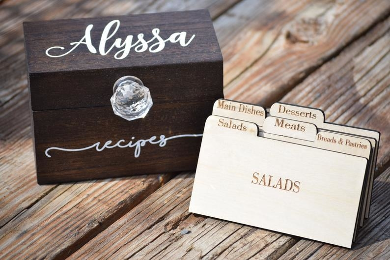 """dark brown wood recipe box that says """"Alyssa"""" on the lid and """"recipes"""" on the front in white script plus wood box dividers for salads, breads, meats, mains, and desserts"""