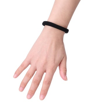 The thick, black hair tie on a wrist