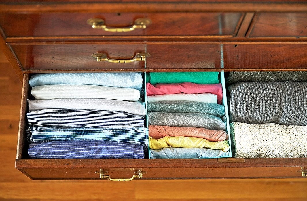 "A dresser drawer organized with ""filed"" folded tees, pants, and sweaters; the tees are in a shoebox"