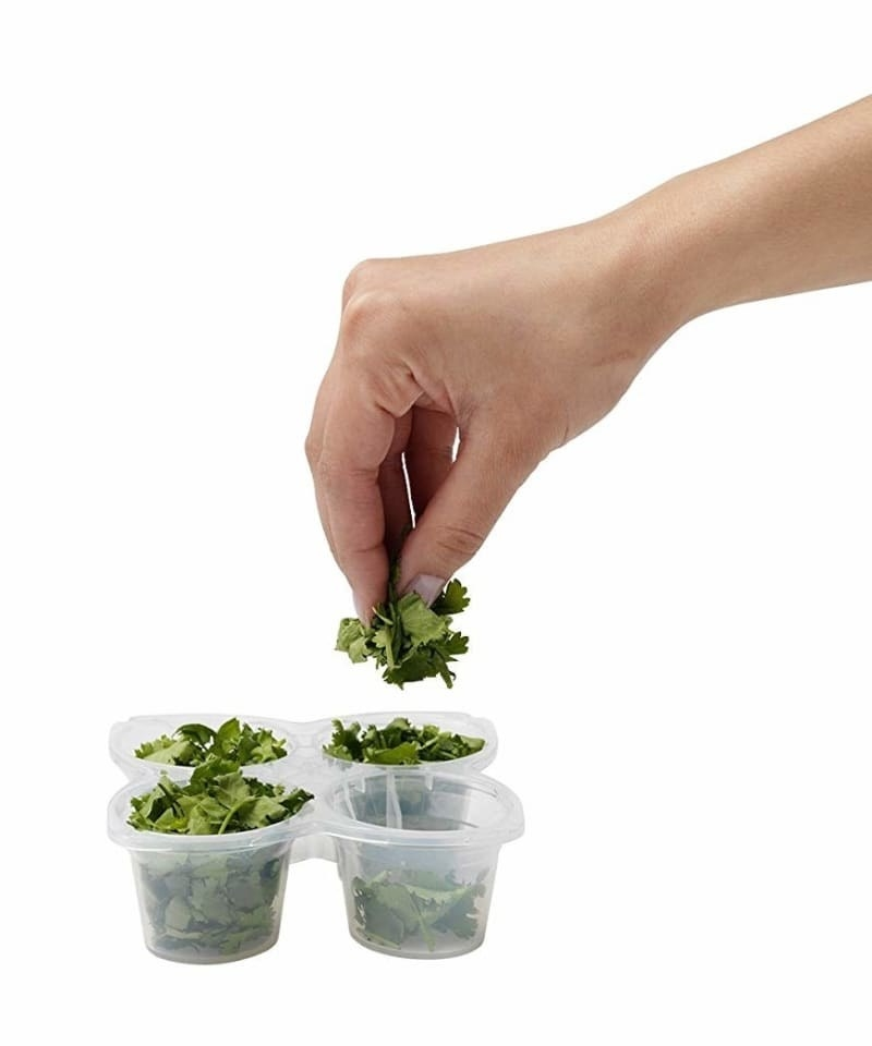 The four-cup tray with herbs in it and a hand grabbing some out of one of the cups