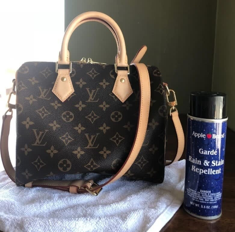 Reviewer photo of the can of repellent sitting next to a Louis Vuitton purse with a towel under it