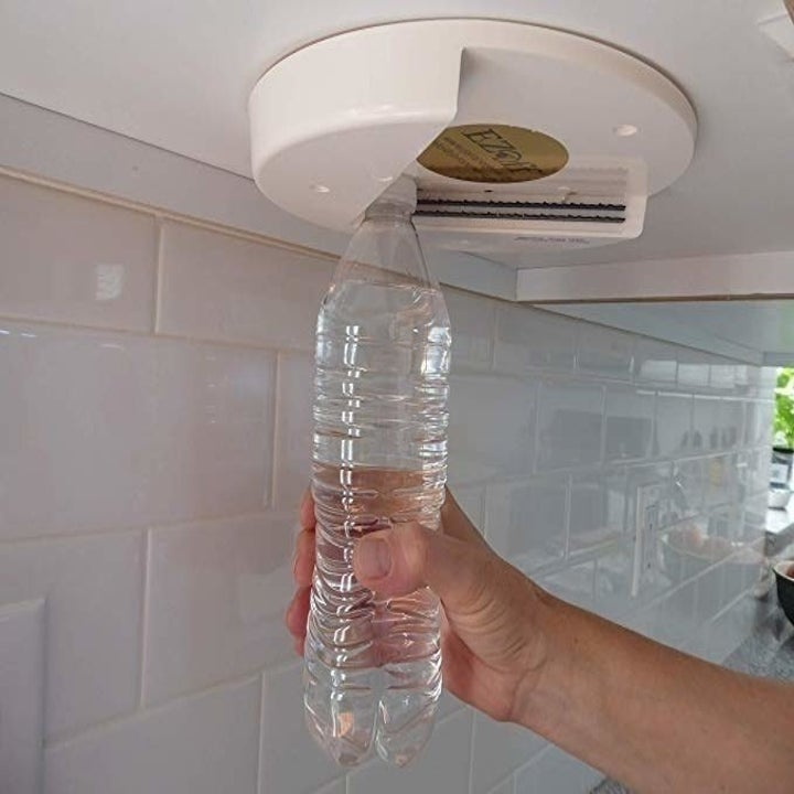 Model's hand putting a plastic water bottle in the corner of the jar opener that's attached to the underside of a cabinet to open the lid