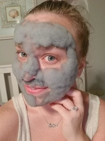 reviewer using foaming gray face mask