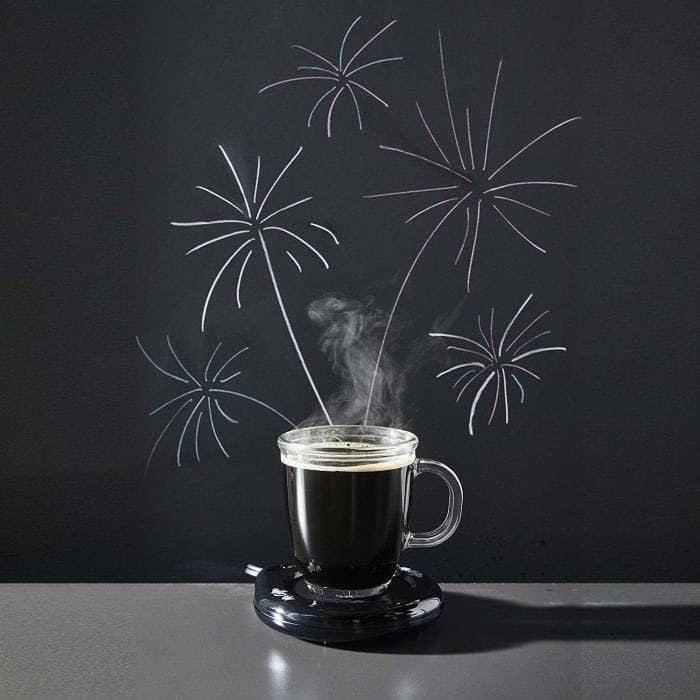 The black circular mug warmer with a clear cup of coffee sitting on top of it