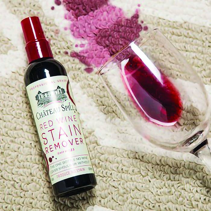 The bottle of red wine stain remover sitting on the carpet next to a spilled red wine glass