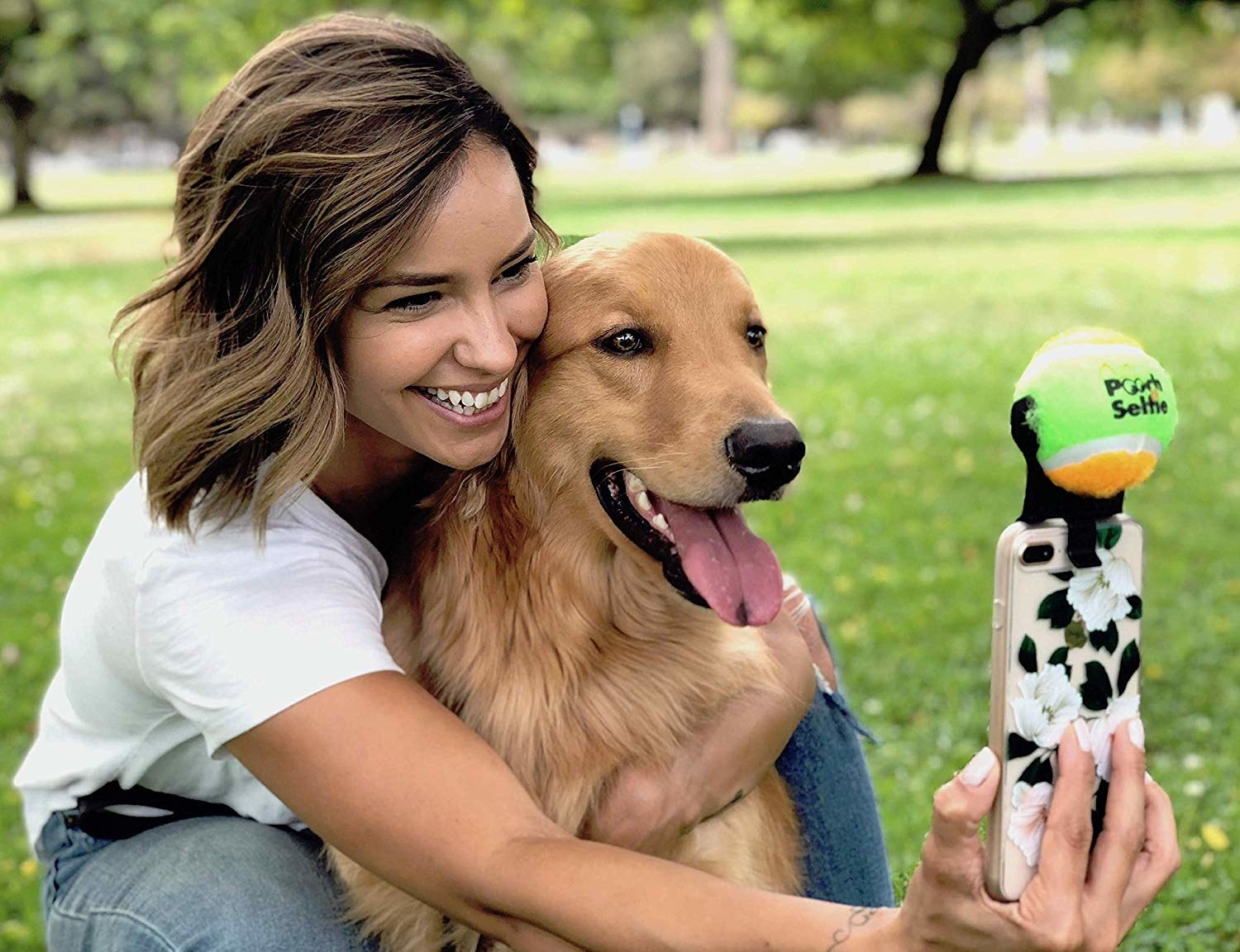 A person holding their dog and taking a selfie. The dog is looking right at the tennis ball attached to the phone.