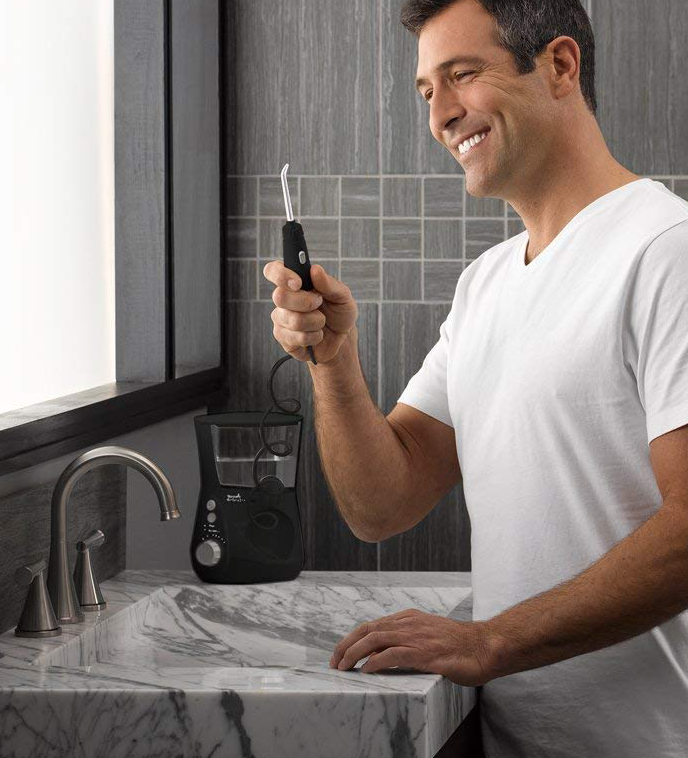 A man smiling at the water flosser