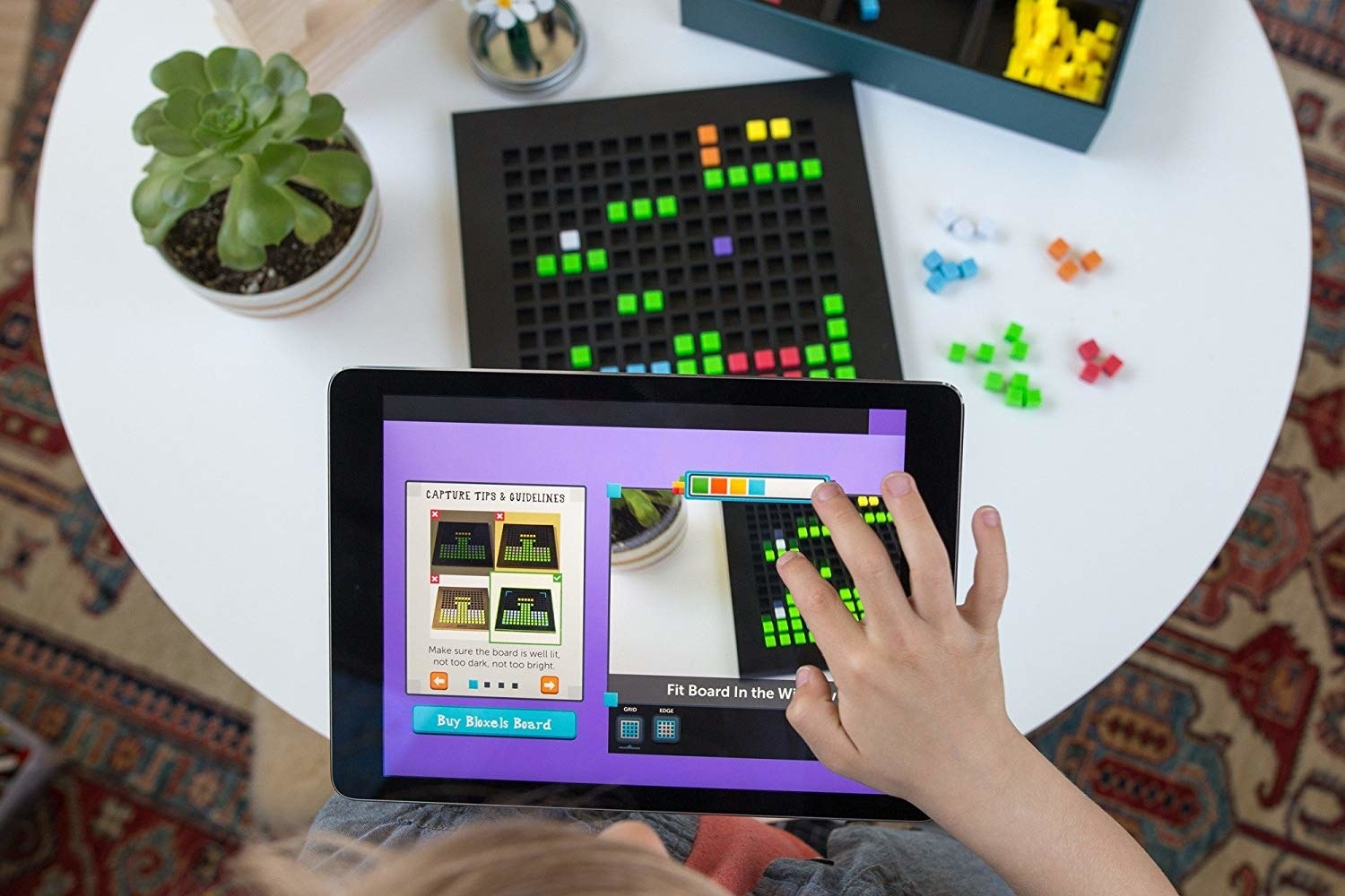 A child using their iPad to create a game from the pattern block board