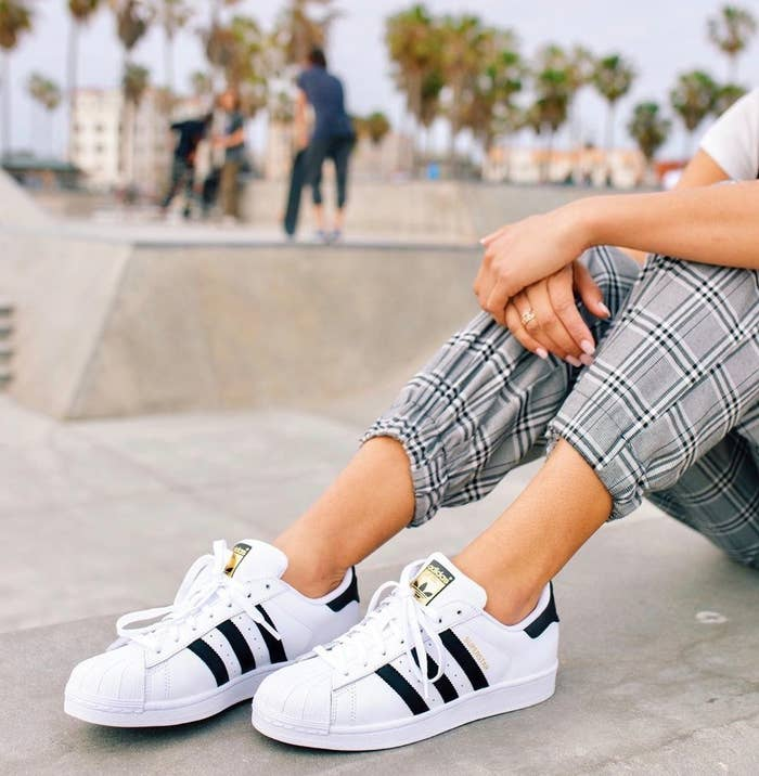 model wearing superstar sneakers in white and black