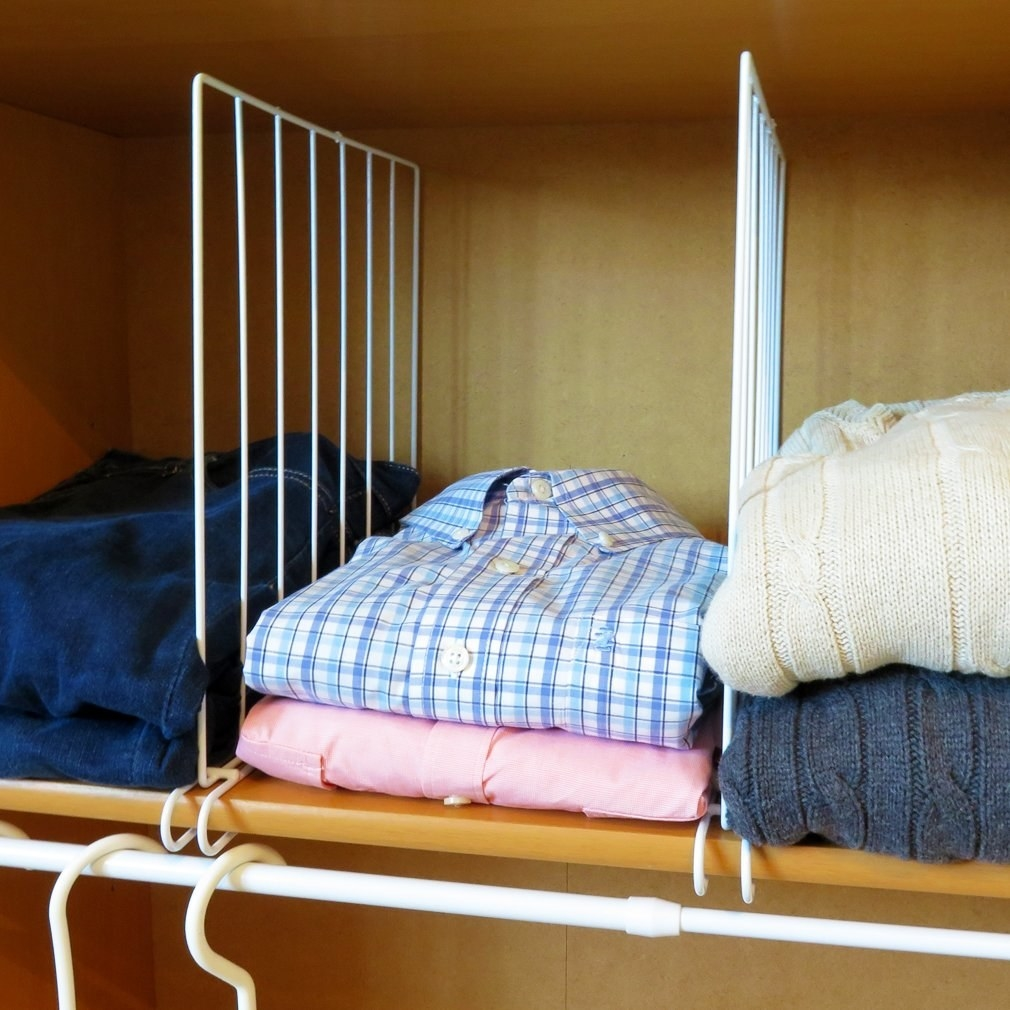 open shelf with vertical white wire dividers to keep vertical stacks of clothes neat