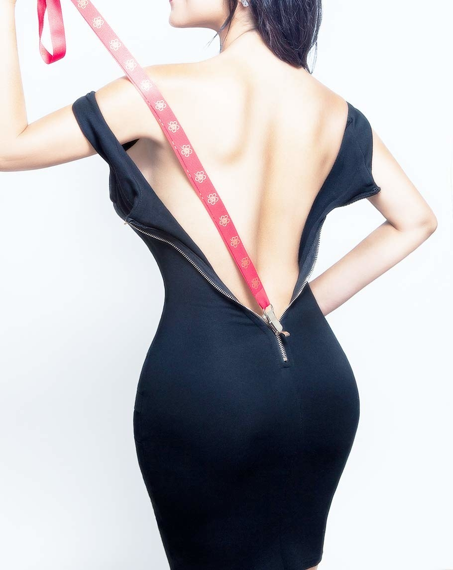 The back of a model with an open dress and the Zipuller in red attached to the back zipper ready to zip up the dress