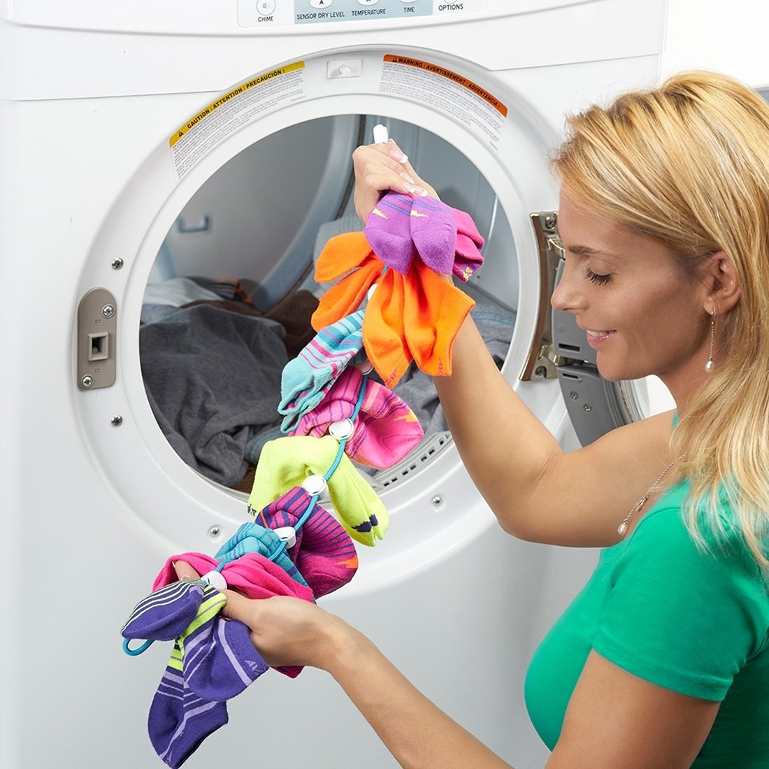 Model holding the long wire SockDock with circles to attach socks, filled with sock pairs next to a washing machine