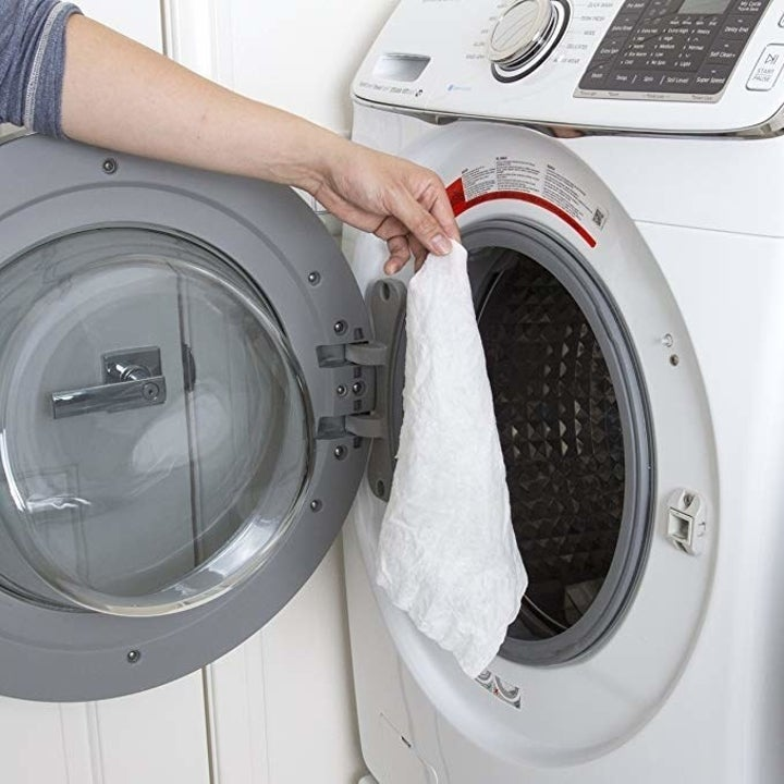 person tossing towel into washer