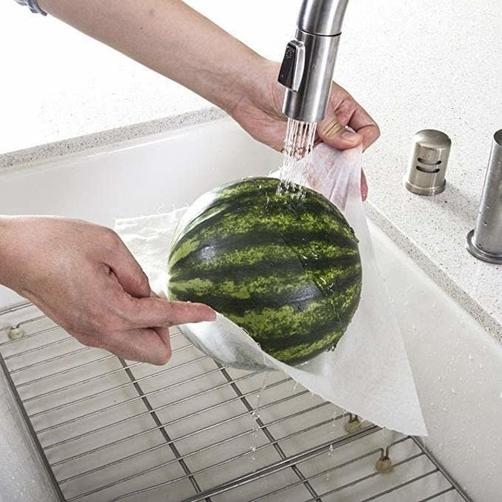 person washing a melon and holding it with the durable towel