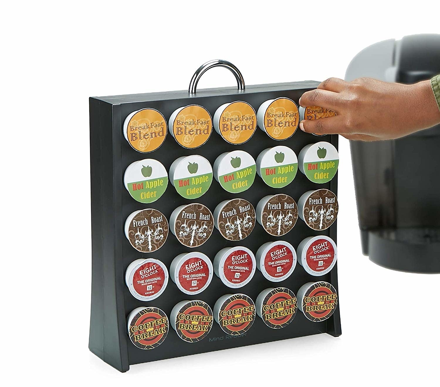 hand putting a K-cup coffee pod into the organizer that contains 25 cups in upright stand