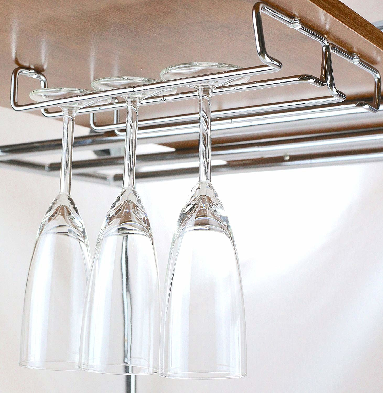 silver wine glass rack mounted on the underside of a kitchen cabinet so glasses are stored vertically and upside down