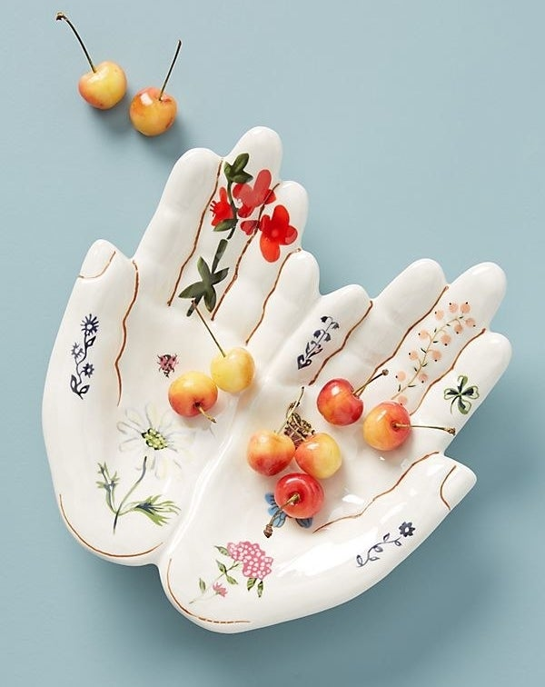 A white bowl in the shape of two hands pushed together. The finger lines are detailed in gold and there are flowers painted on the palms and up the fingers.