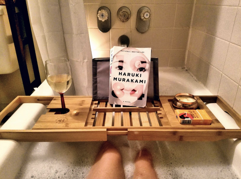 long wooden tray that stretches across the entire tub. it has a book, wine glass, and candle sitting on top of it and the reviewer's legs are shown underneath, soaking in sudsy water.