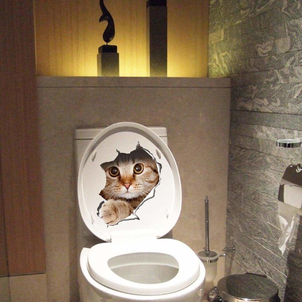 Toilet lid lifted to reveal image of a cat peeking out