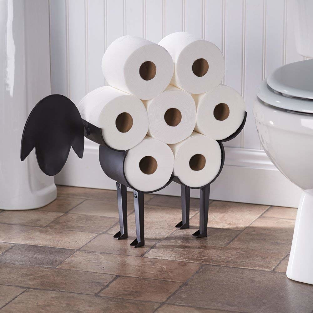 A metal stand in the shape of a sheep's head and feet, with a stand for rolls of toilet paper on the back that makes it look like wool when the toilet paper is stacked together